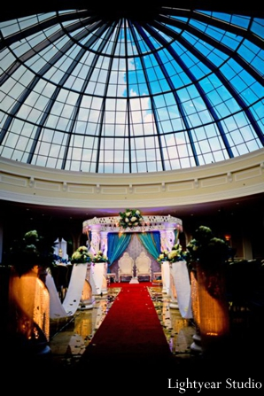 A white pillar mandap under a glass domed ceiling.