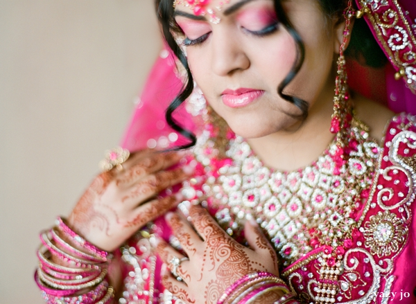 Indian bride in pink wedding lengha and bridal hair and makeup ideas