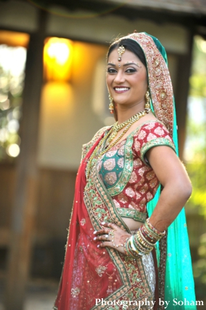 Indian bride in red, white and green wedding lengha.