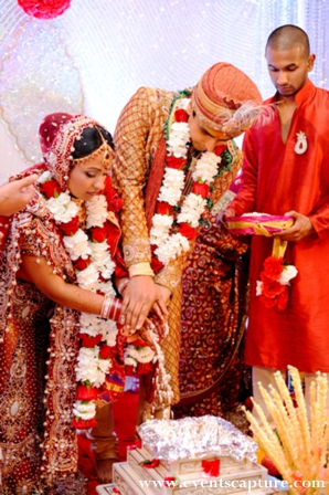 Indian bride and groom wear traditional wedding outfits and jaimala flower garlands.