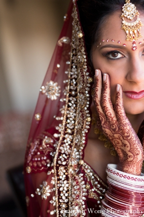 Indian bride in rose wedding lengha and bridal mehndi on hands