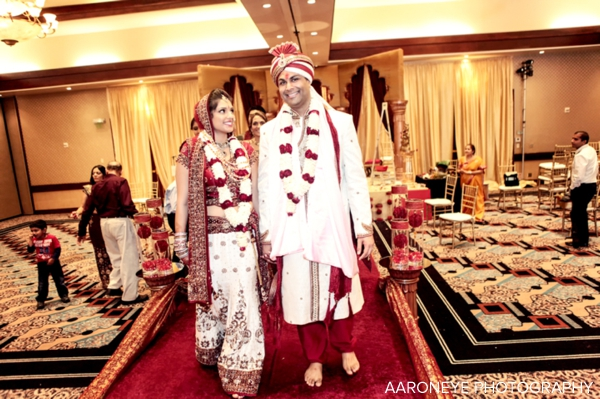 Indian bride and groom walk out of their traditional indian wedding ceremony.