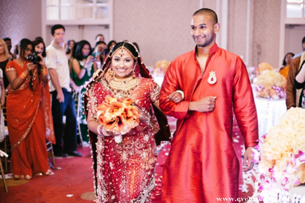 Indian bride in red wedding lengha walks into her indian wedding ceremony