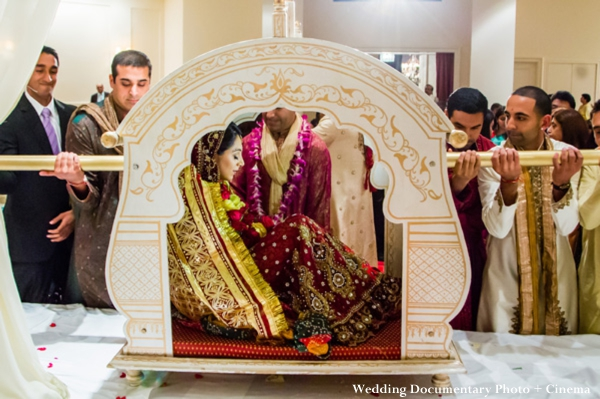 Indian bride arrives to indian wedding ceremony in a palanquin.