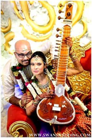 South Indian bride and groom take portraits with sitar.
