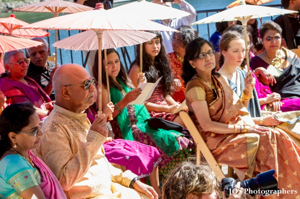 indian wedding guests with parasols at outdoor south indian wedding
