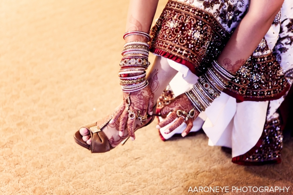 Indian bride puts on bridal wedding lengha and bridal shoes