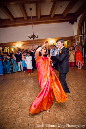 Indian bride wears orange and pink wedding sari.