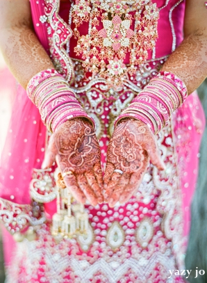 Indian bridal henna on hands on indian bride in pink wedding lengha