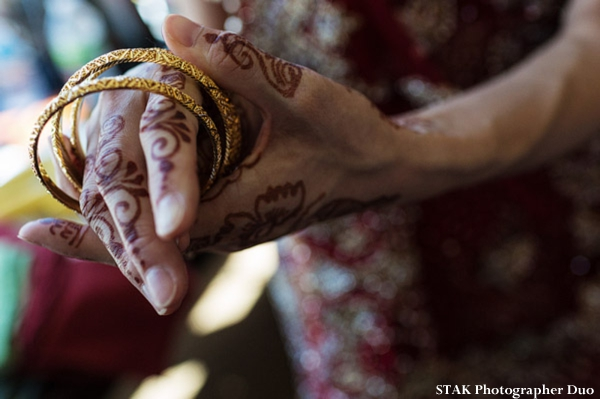Indian bride puts on gold churis on her hands with bridal mehndi