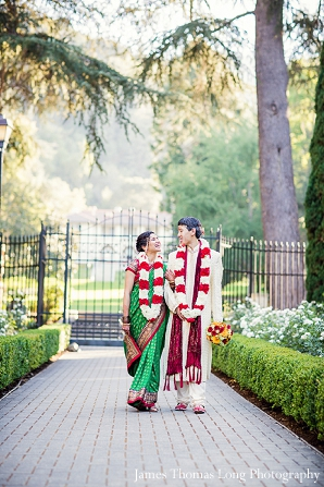 Fusion Indian wedding couple walk with jaimalas.