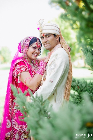indian bride in pink wedding lengha and indian groom in white sherwani