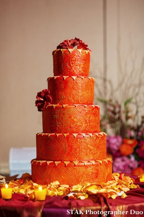 Modern Indian wedding cake in gold, orange and fresh flowers.