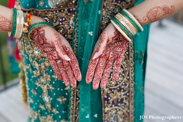 Indian bride with bridal mehndi on hands.